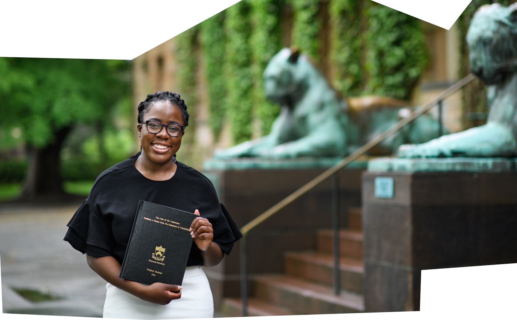 Wilglory Tanjong '18 standing with her senior thesis in front of Nassau Hall in 2018.