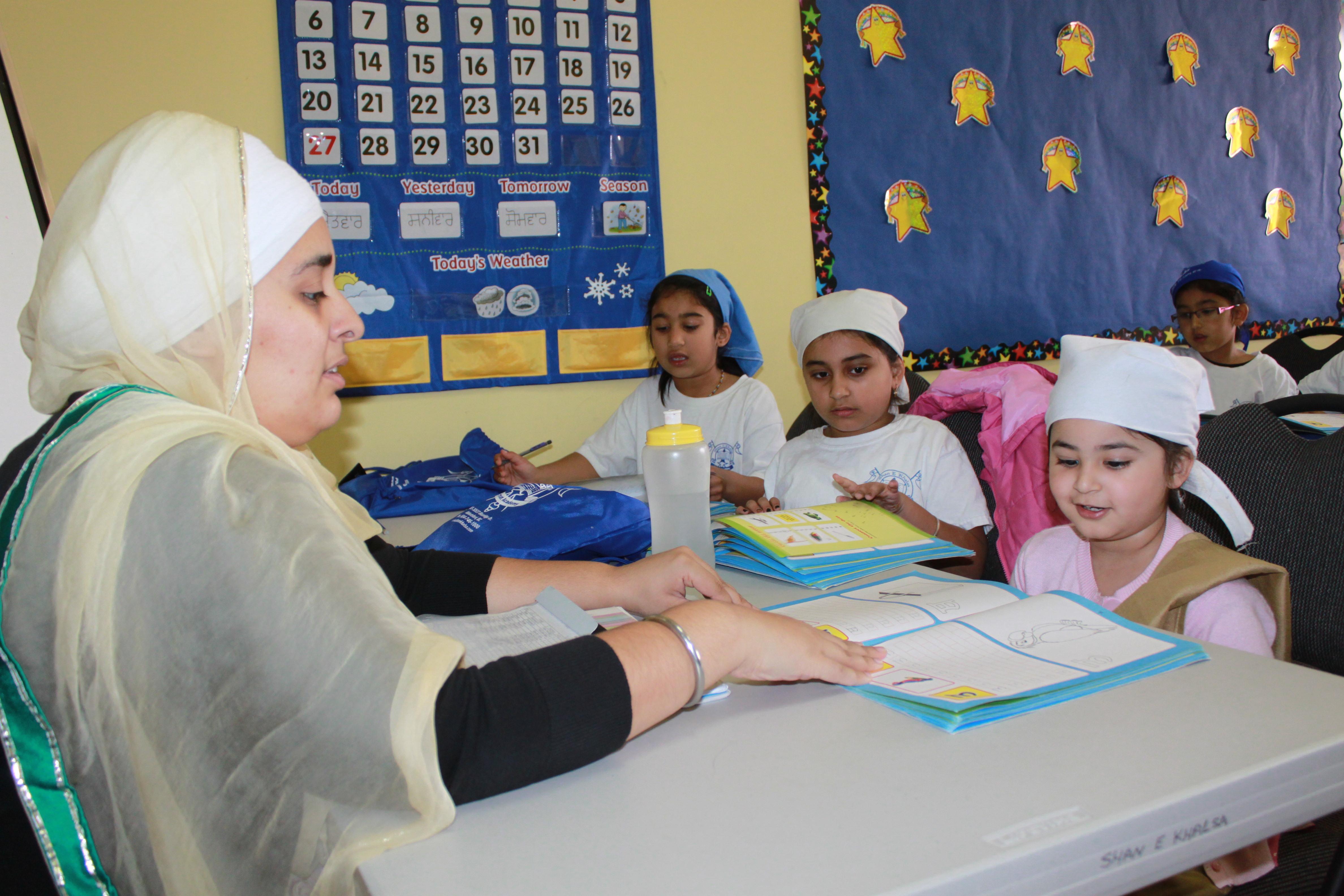 Teacher going through a punjabi workbook with her students