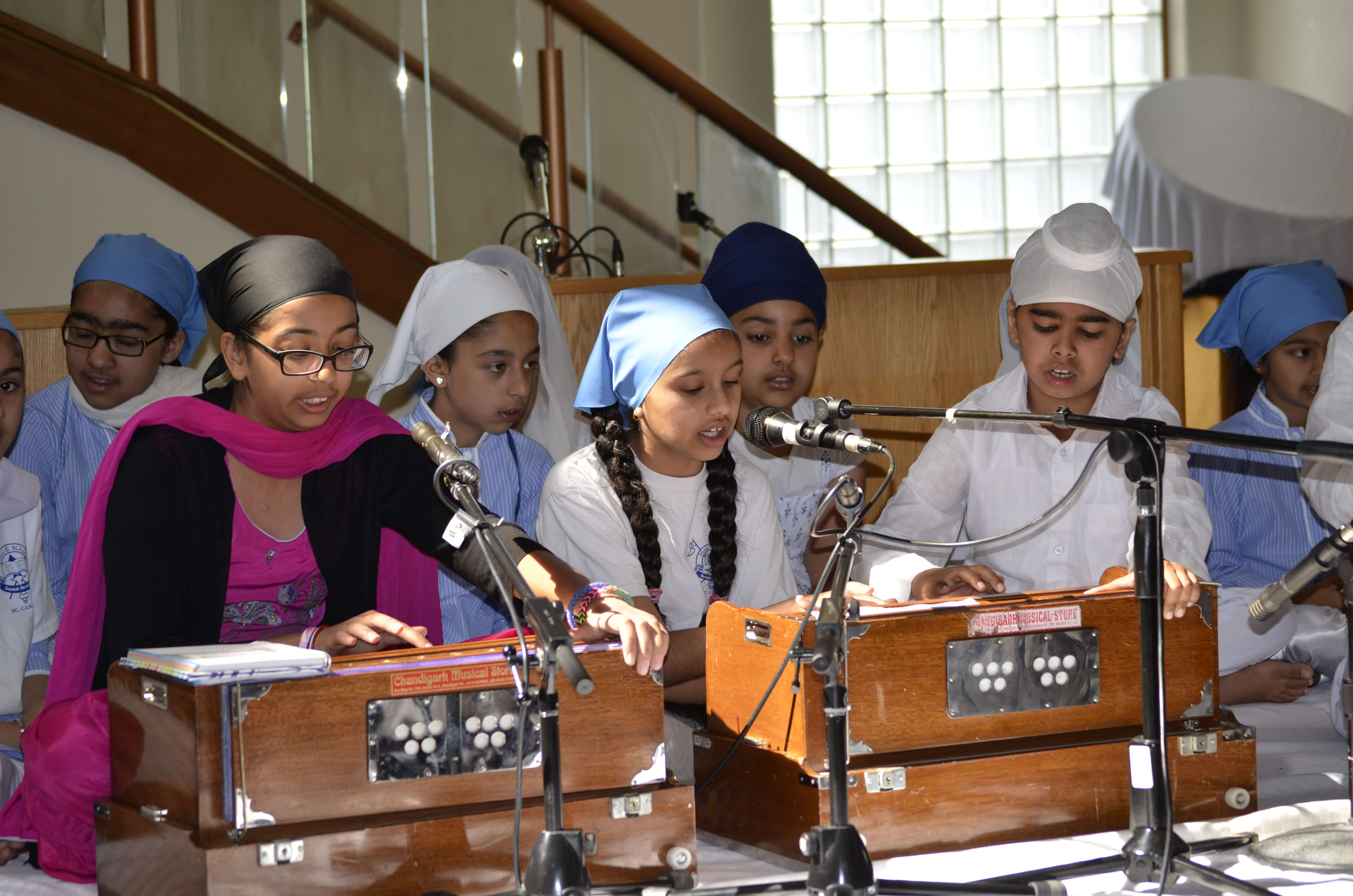 Group of students playing the harmonium on stage