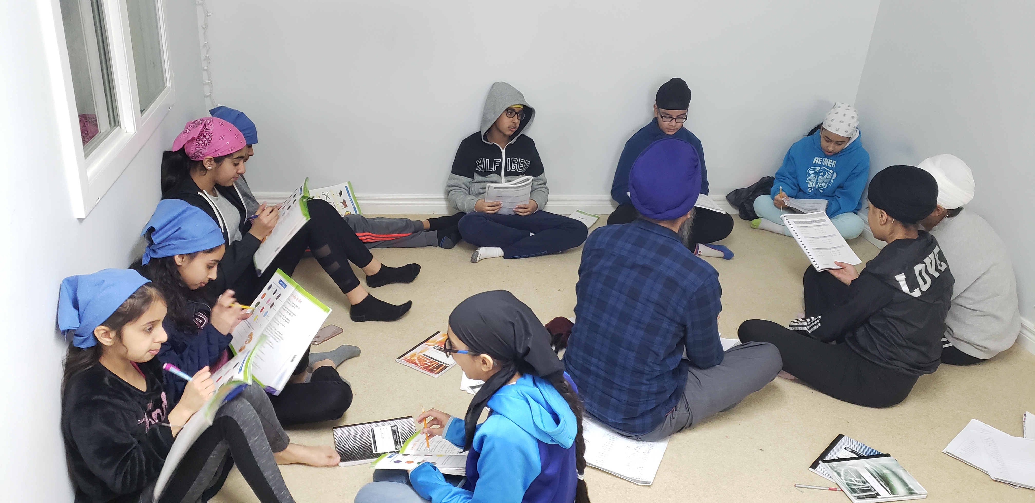 Students sitting down in groups and doing a punjabi worksheet