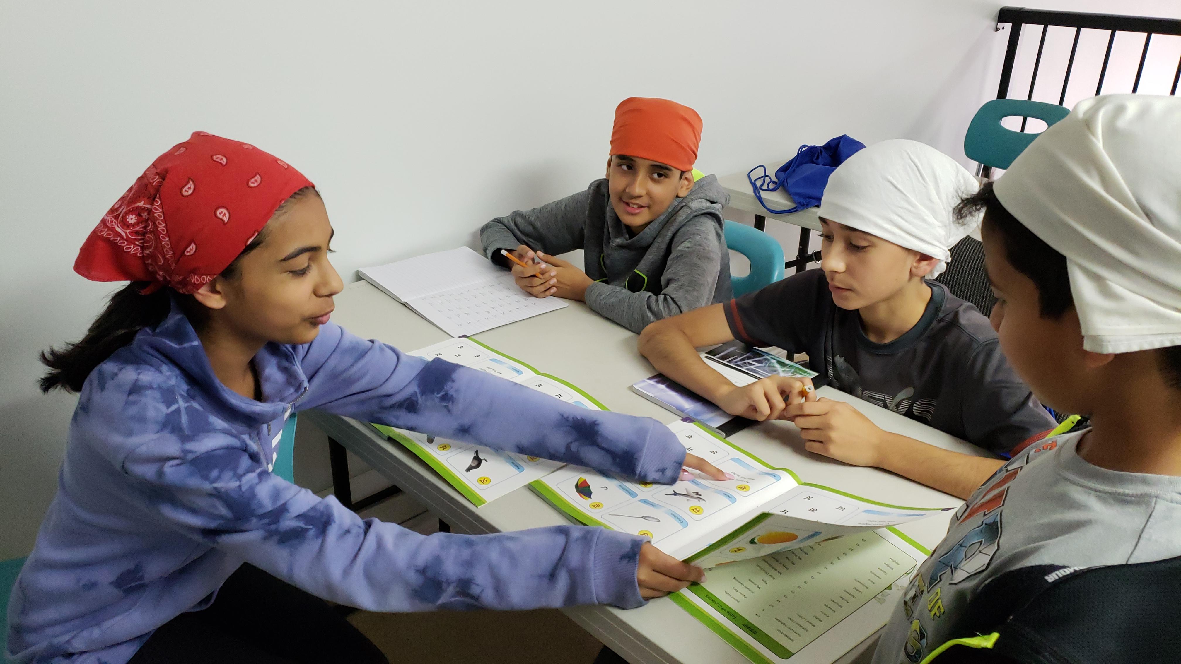 Shan E Khalsa student teacher helping a student read punjabi