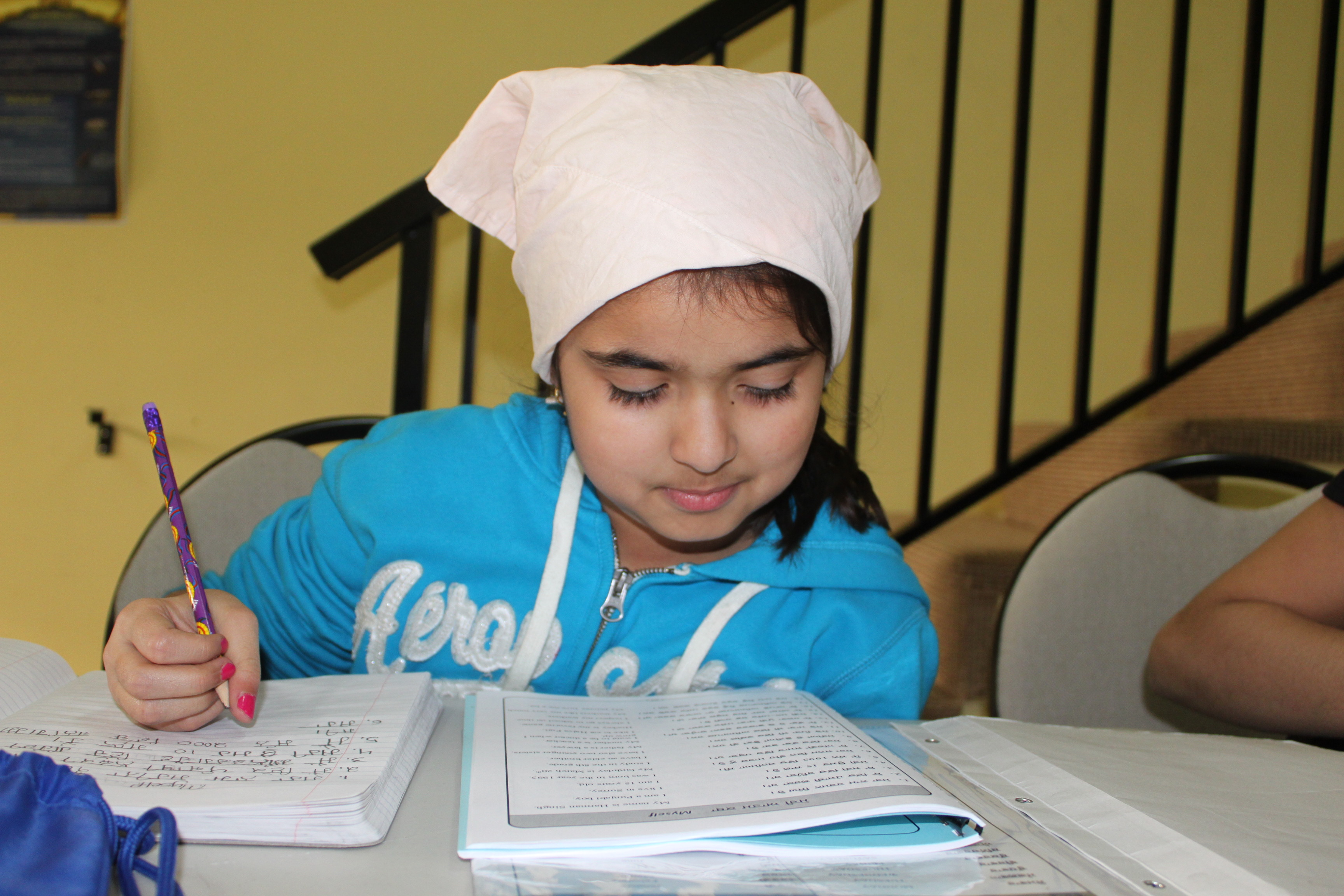 Shan E Khalsa student sitting and doing a punjabi worksheet