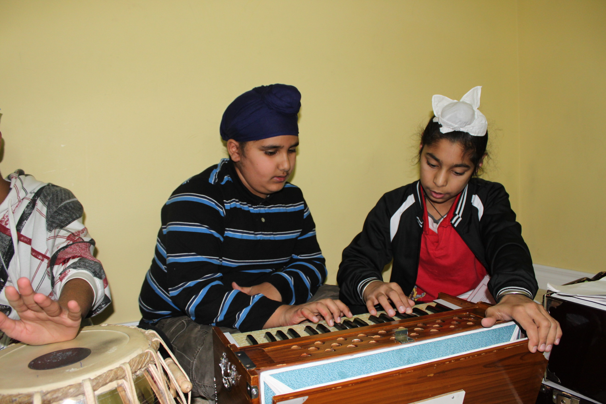 Two students playing the harmonium