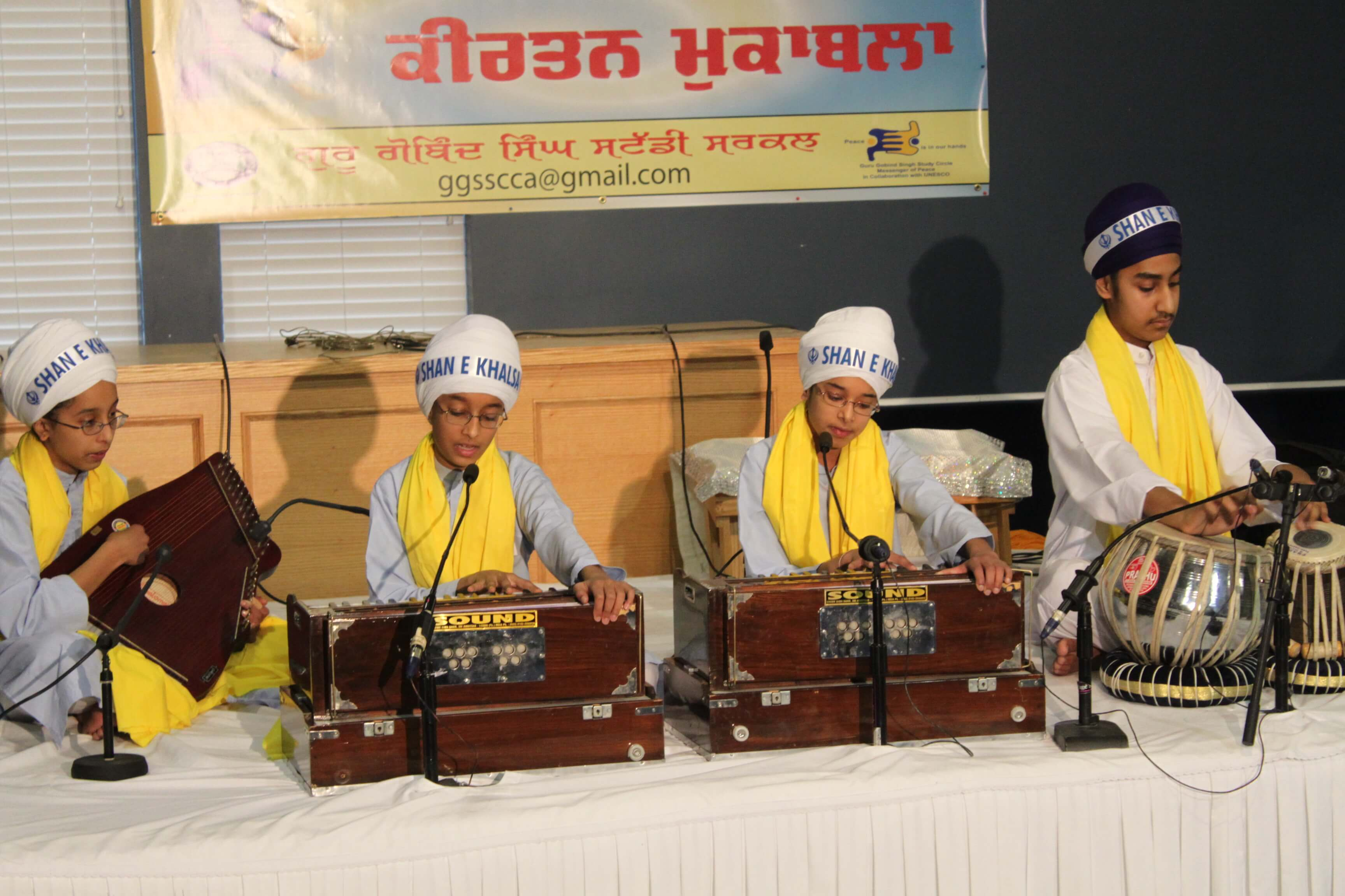 Group of students playing the harmonium and tabla (indian hand drums) on stage