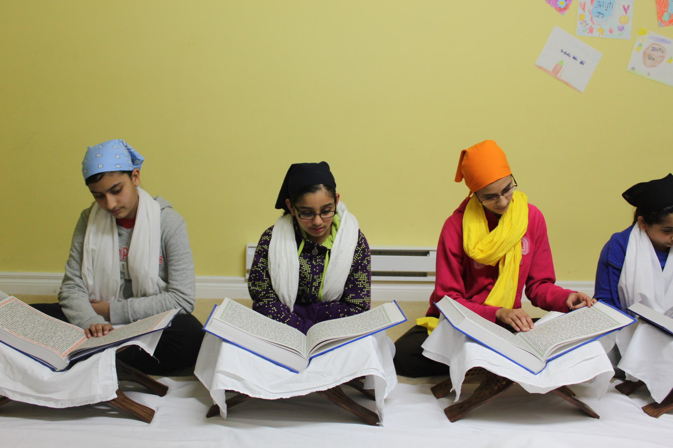 Group of students are sitting on the ground reciting Paath from a Sainchi (Religious scripture)