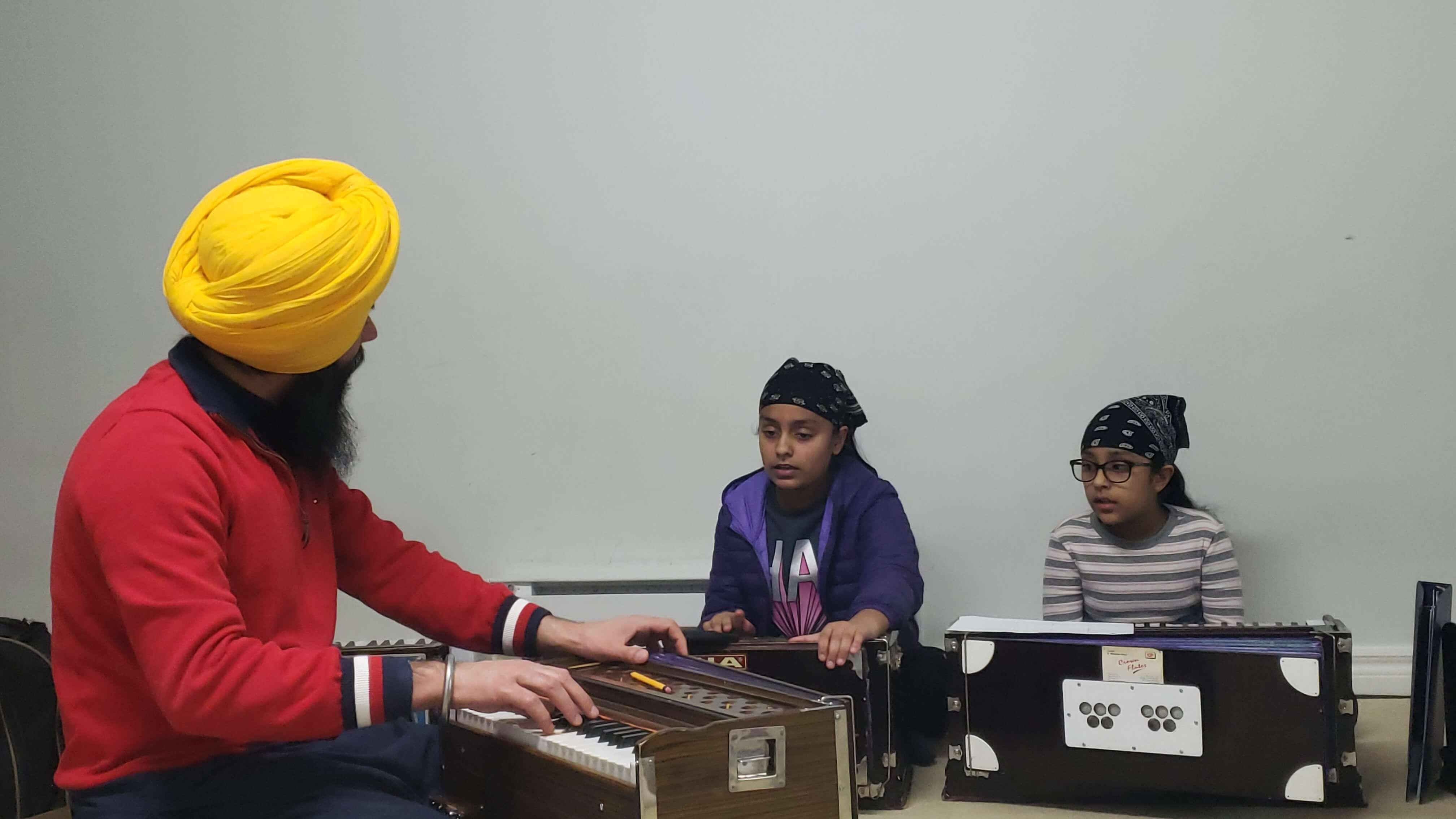 A teacher teaching 2 students how to play the harmonium
