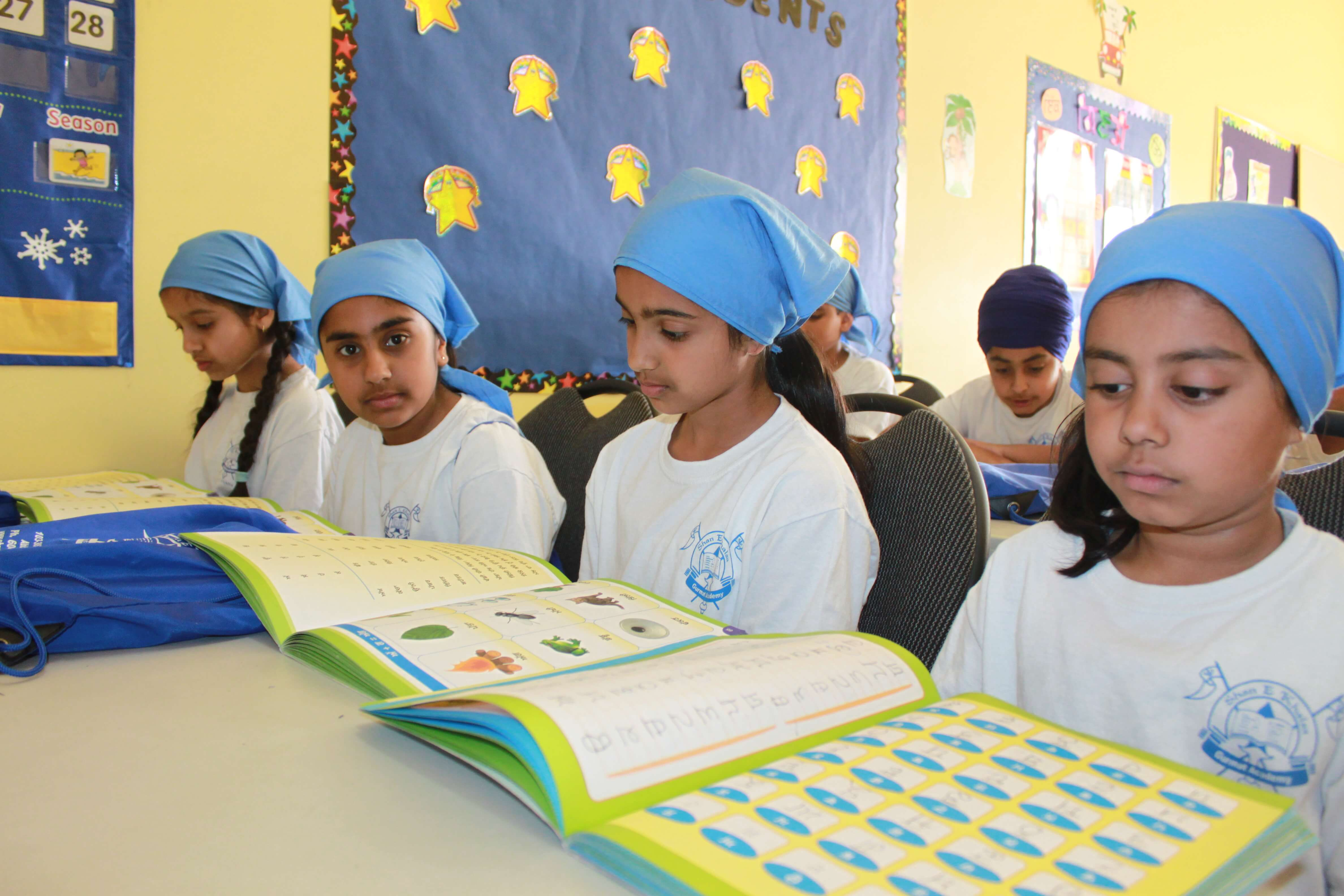 Group of students reading from a punjabi workbook