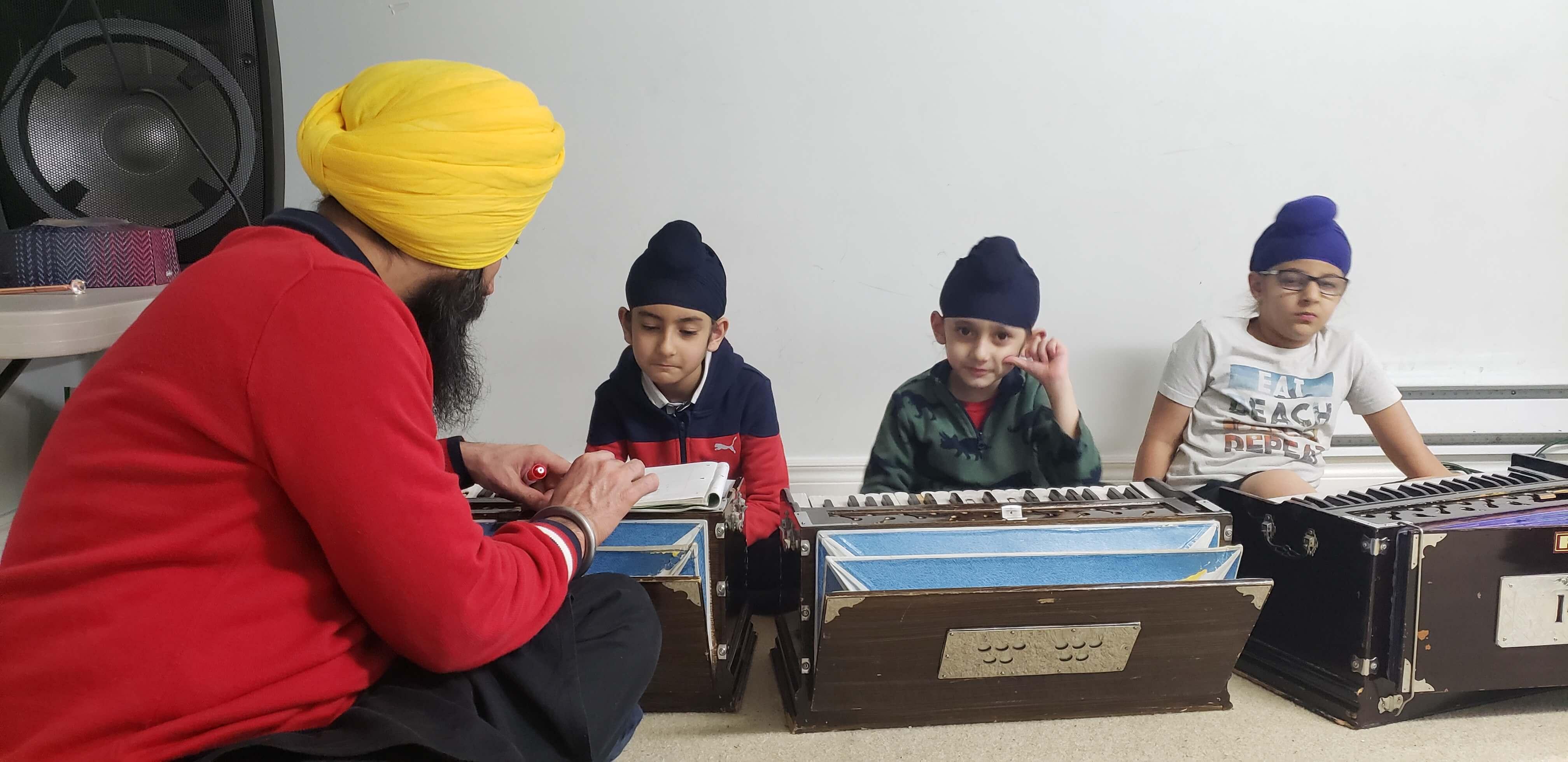 A teacher teaching 3 students how to play the harmonium