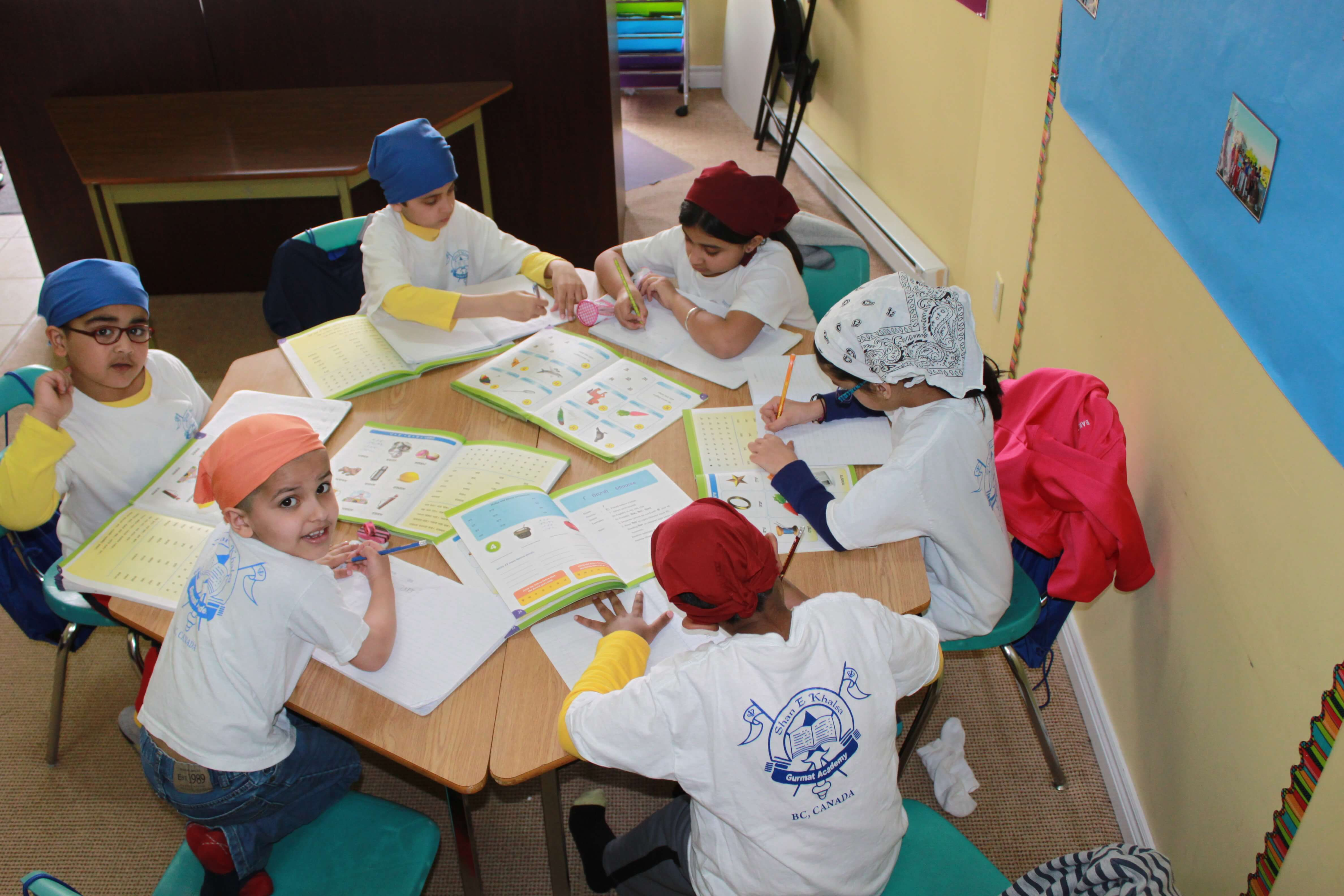 Group of kids sitting at a table and doing a punjabi worksheet