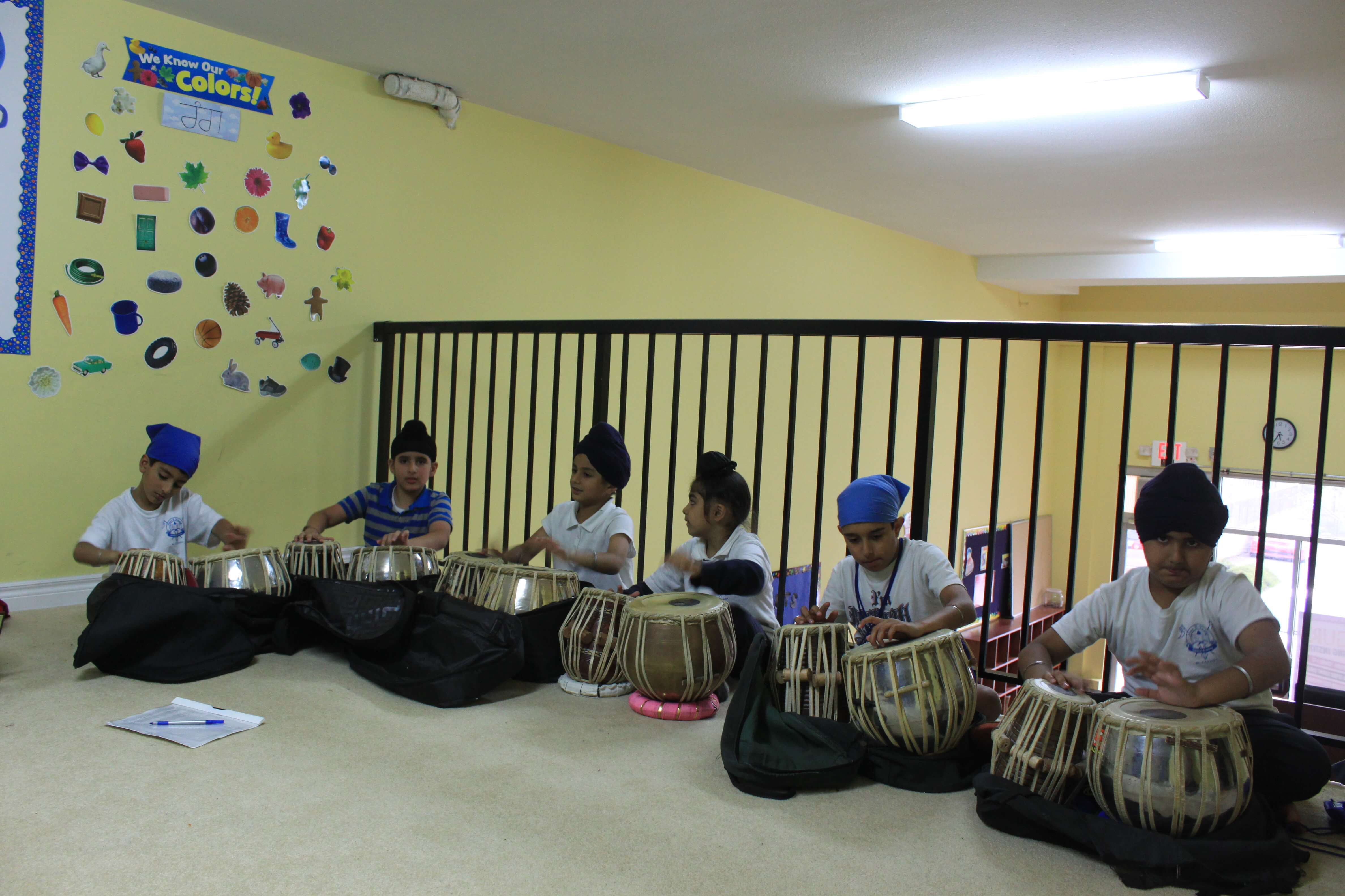 A group of students practicing how to play the tabla (indian hand drums)
