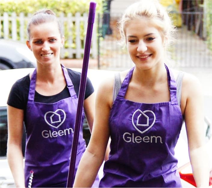 2 Gleem Home / House Cleaning staff members standing at a house with cleaning equipments.