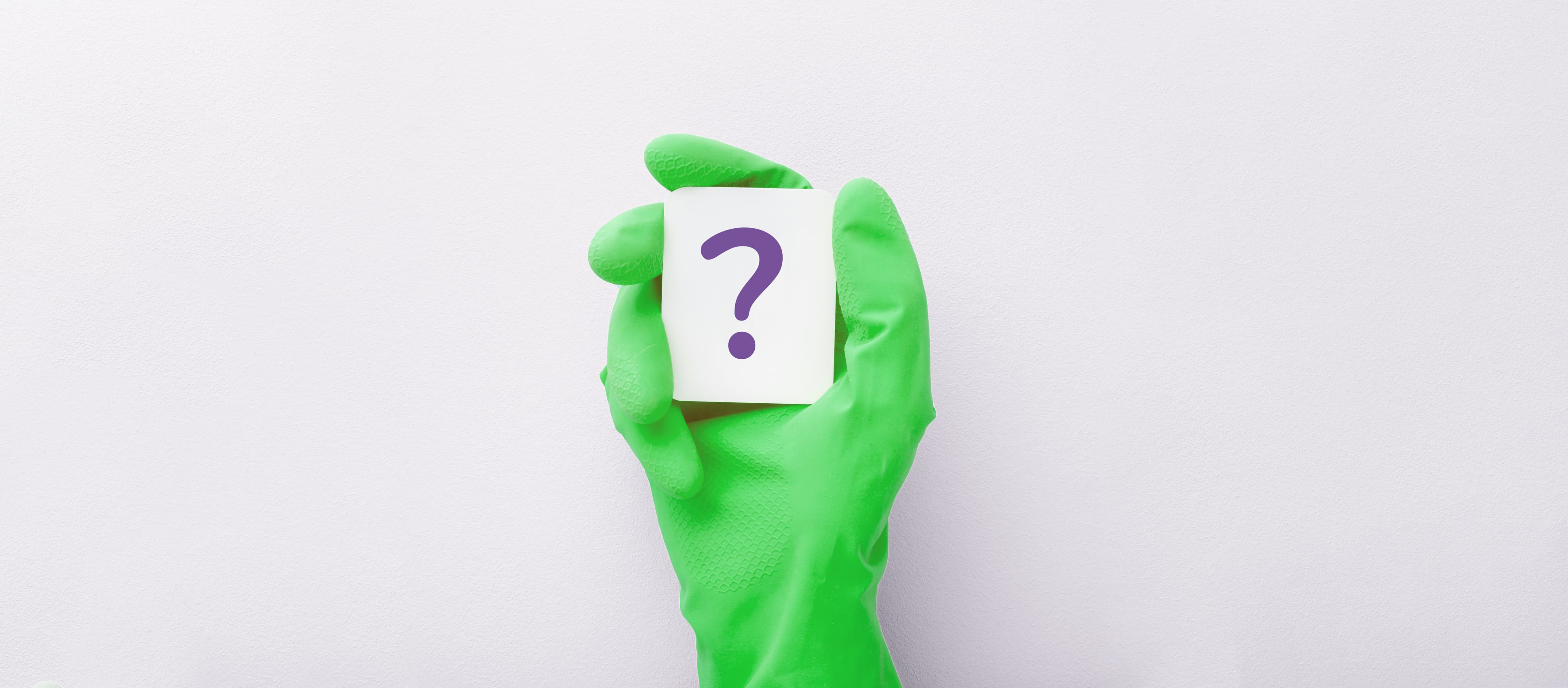 A hand in green rubber gloves holding a card with a question mark on it.