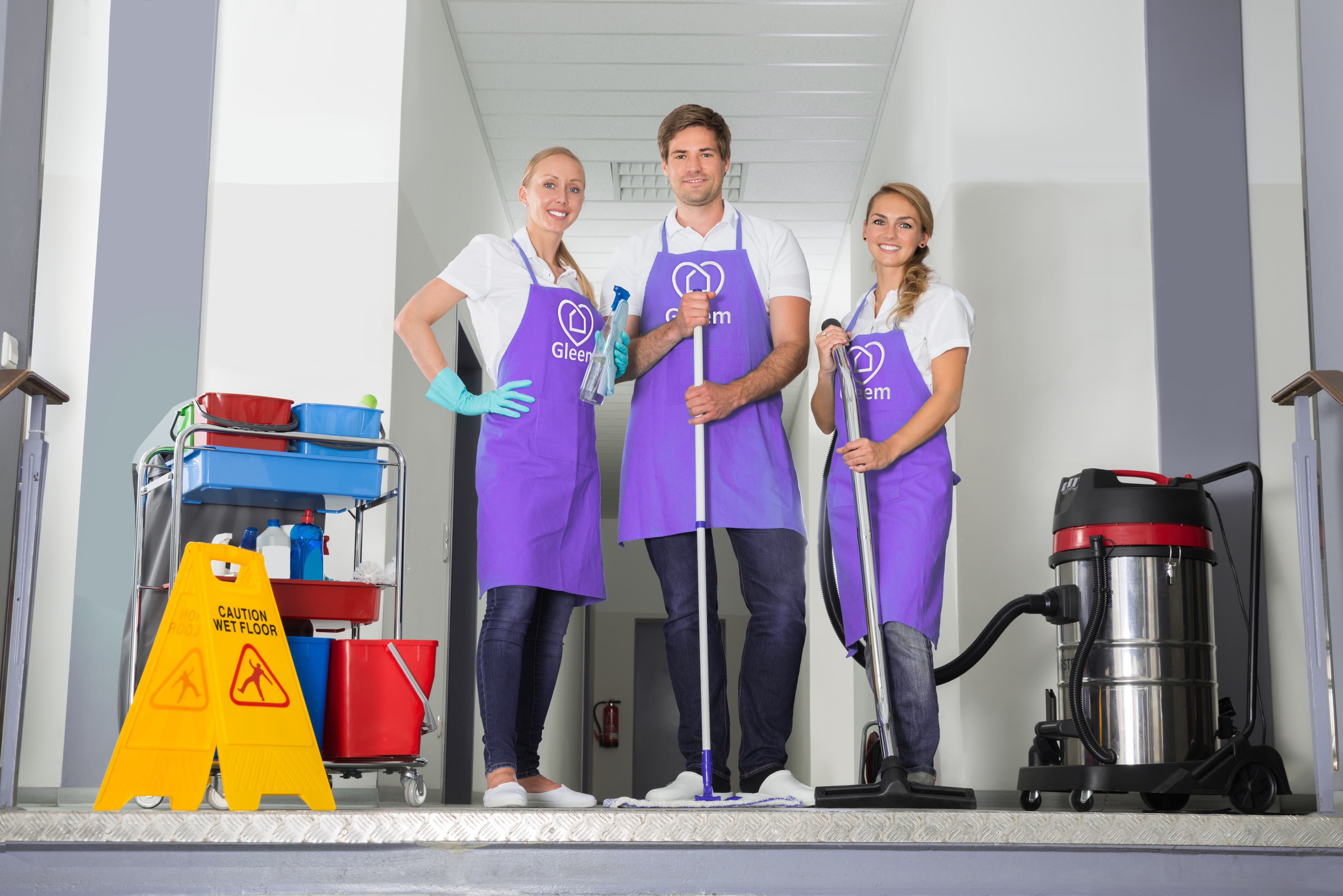 3 Gleem Commercial Cleaning staff members standing with cleaning equipment..