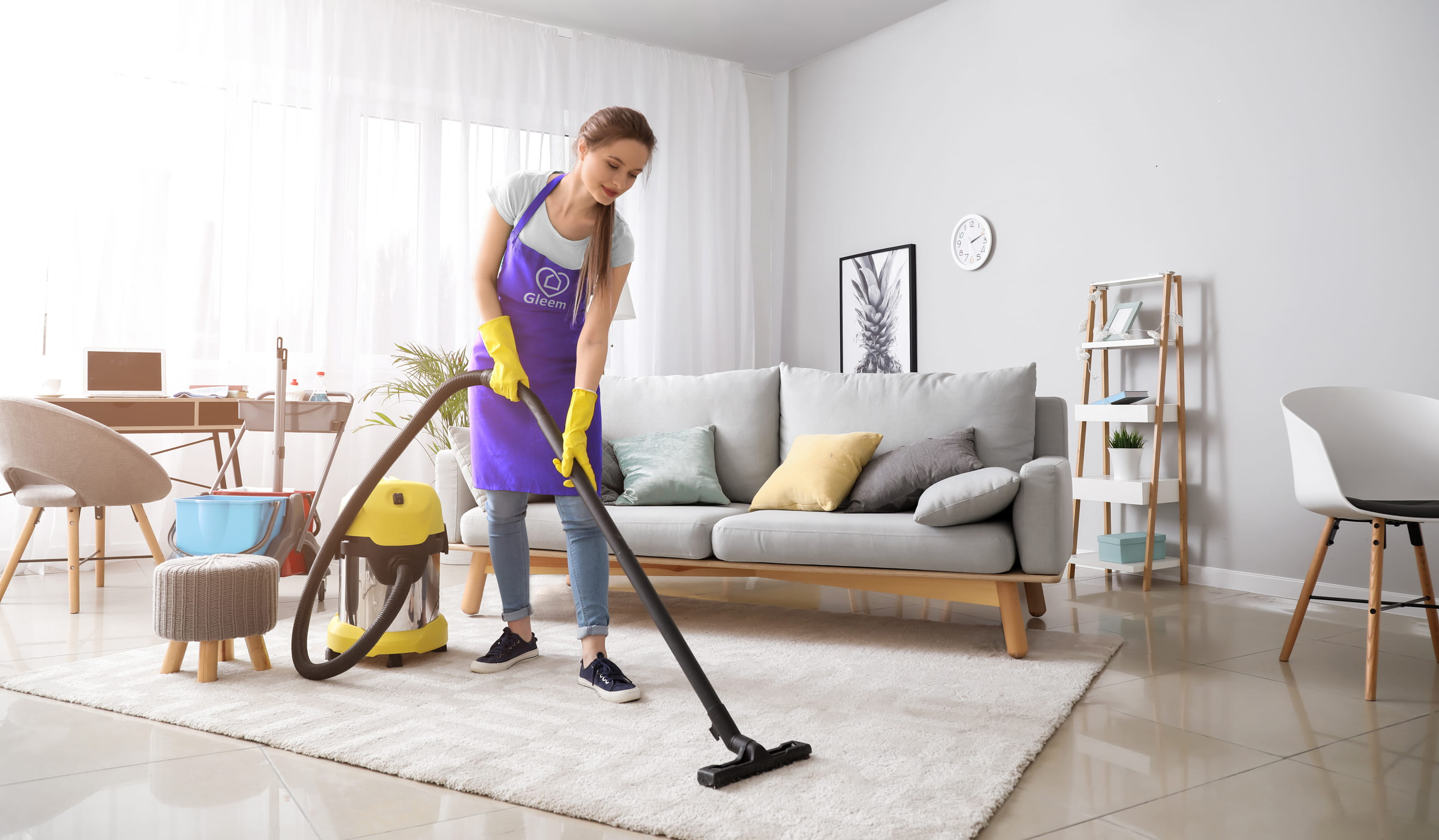 Gleem Home / House Cleaning staff member vacuums the floor carpet.