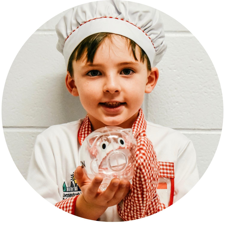 A boy in a chefs uniform holds a piggy bank.