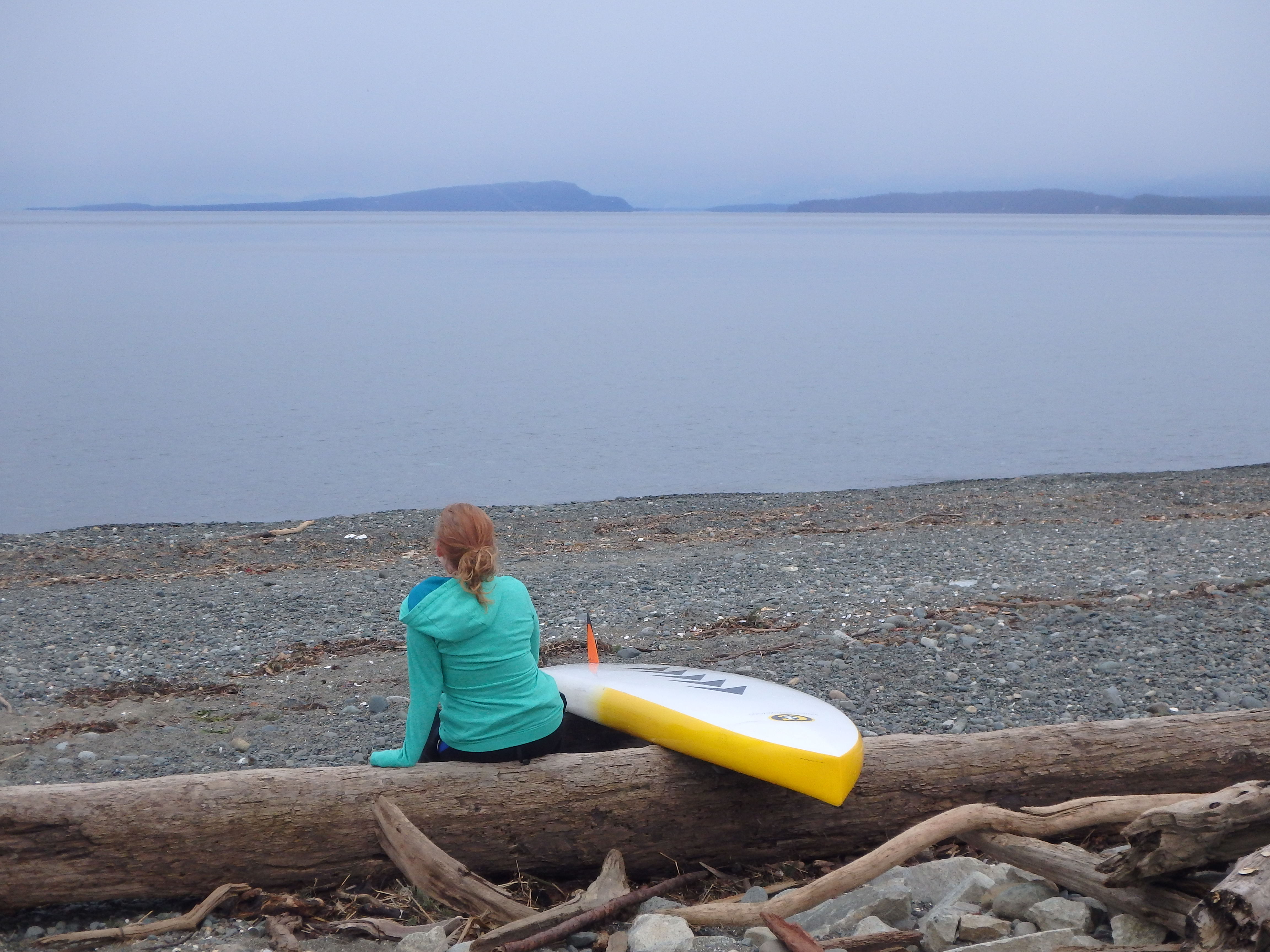 Sitting and looking at the ocean with a stand up paddle board.