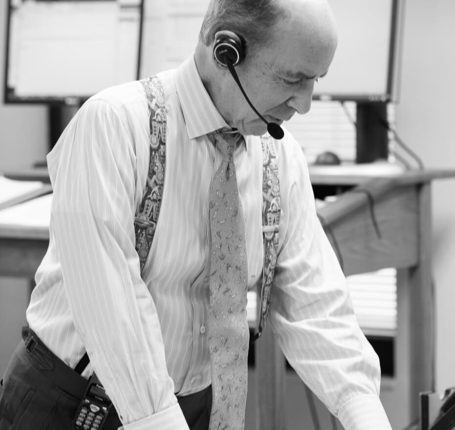 Mr. John B Levy wearing a headset in an office.