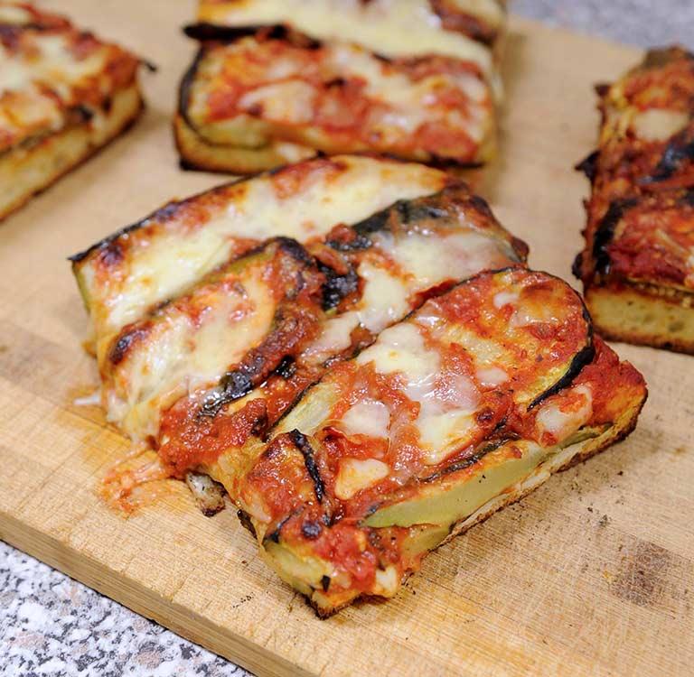 Focaccia Parmigiana von Bäckerei Fenuta (geschnitten à 10x15cm)Mit: Zucchini, Auberginen und Mozzarella