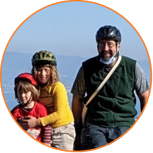 Zach and boys smiling while wearing bike helmets