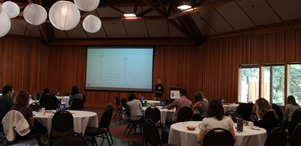 Eric Lam presents at ILN in front of a room of healthcare innovators.