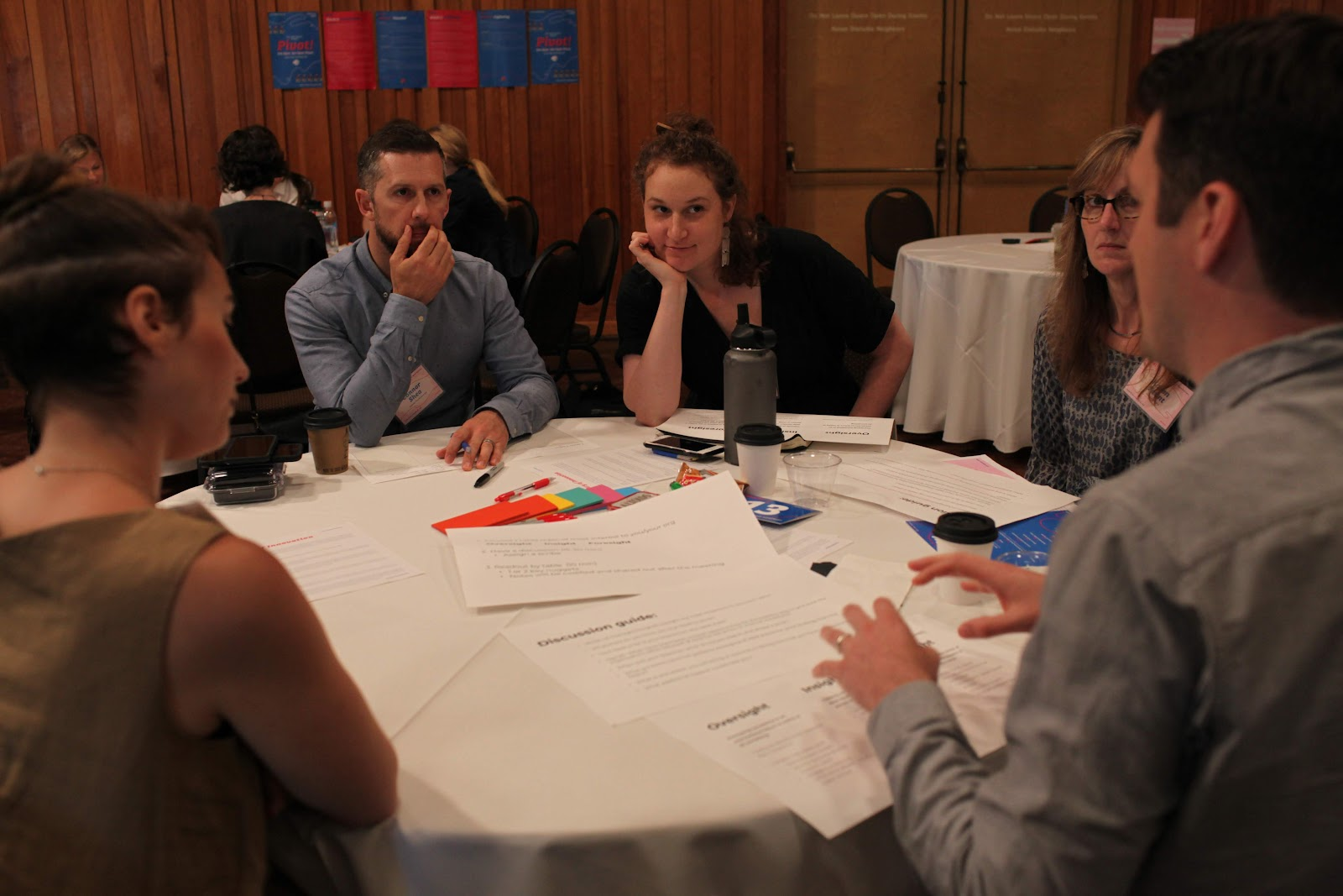 A group of six ILN attendees meet together around a table.