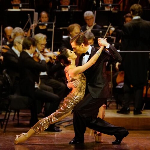 a picture of a dance couple in front of an orchestra
