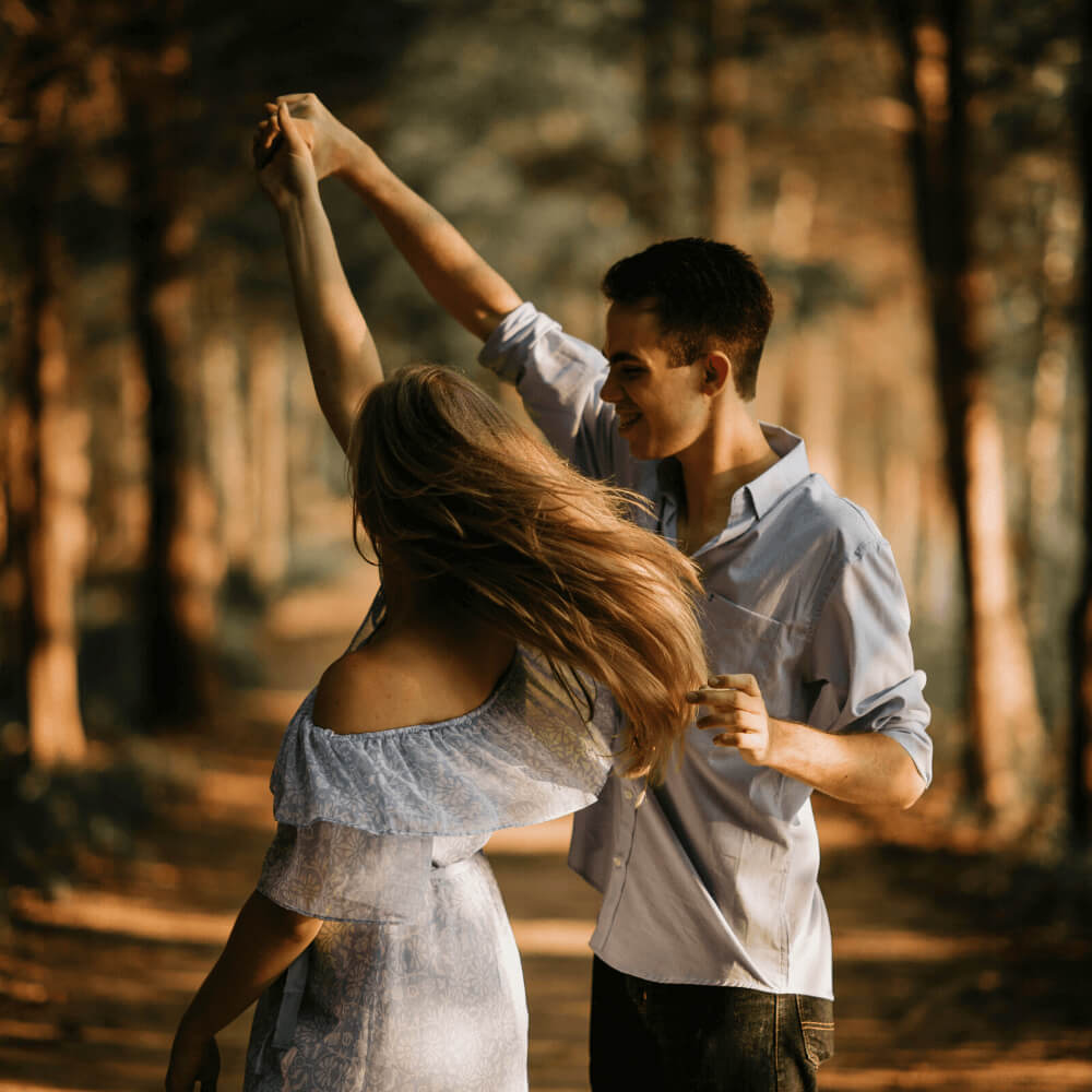 a picture of couple dancing in the forest