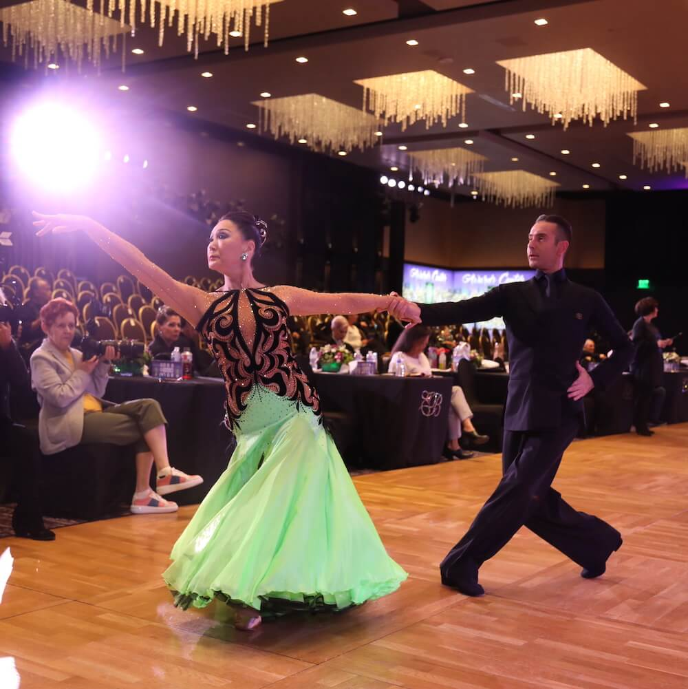a picture of pro-am dance couple dancing the foxtrot