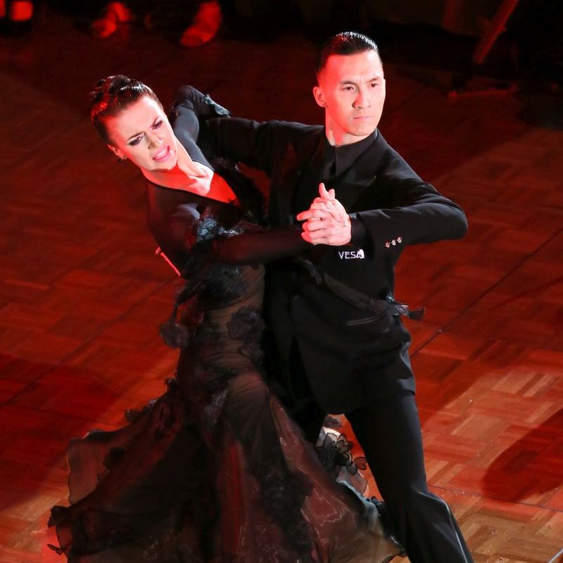 A ballroom dance couple, performing tango in promenade position
