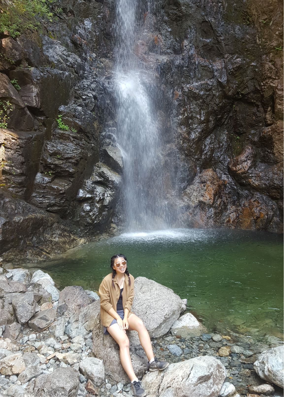 A photo of myself sitting on a rock by a waterfall.