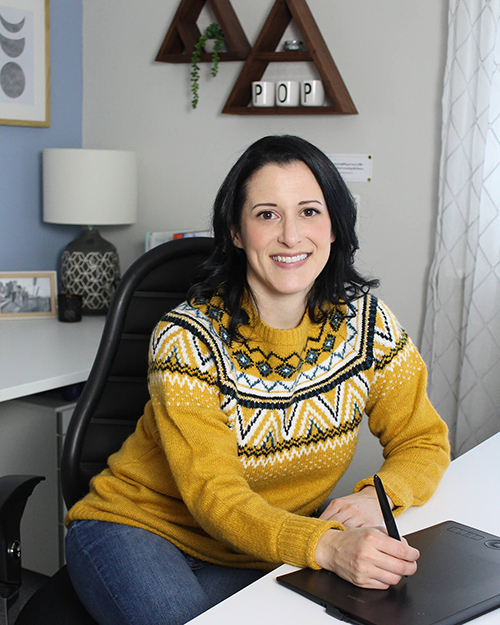 Holly Greiff wearing a yellow sweater sitting in her home office.