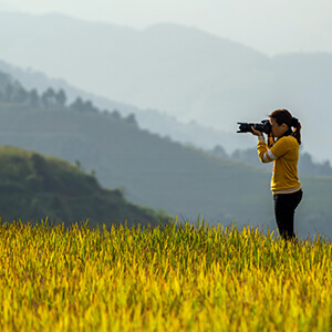 Asian woman taking a professional photograph in the grass with mountains in the background