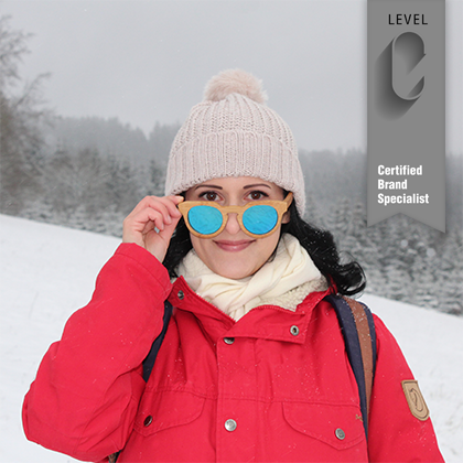 Holly Greiff in the snow wearing polarized sunglasses, a beanie, and a red jacket