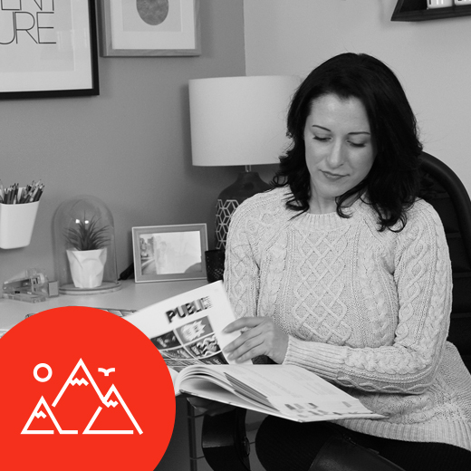 Holly Greiff at Polarized Branding searching conducting brand identity design and looking at brand book in home office