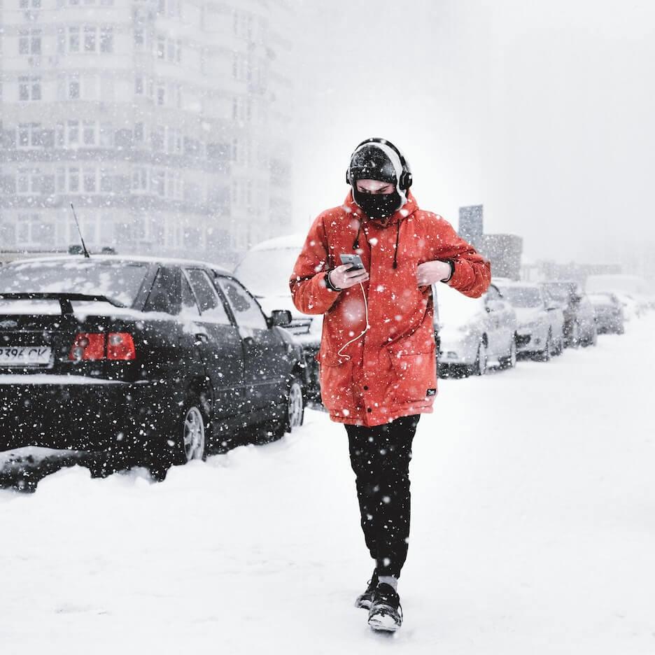 A man walks through the snow wearing headphones. Photo by Victor Xok on Unsplash.