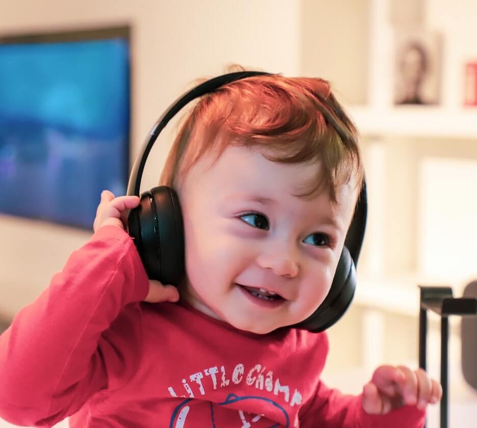A happy baby wearing headphones. Photo by Alireza Attari on Unsplash.