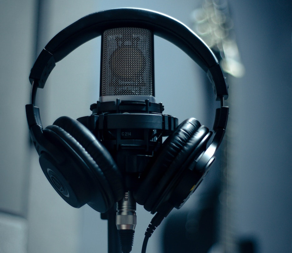 Headphones resting on a microphone. Photo by Wallace Chuck from Pexels.