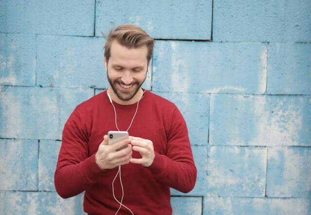 Man in red jumper with earphones. BankNXT podcast. Photo by Andrea Piacquadio from Pexels.