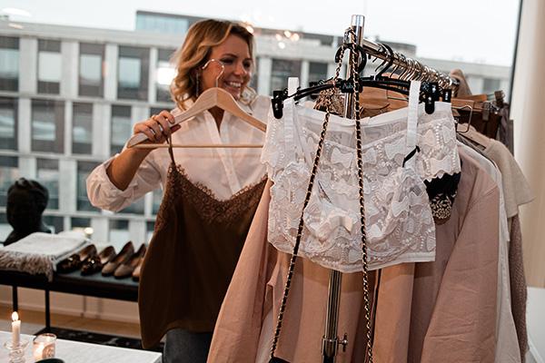 Sarah Nordström hanging clothes on a clothes rack
