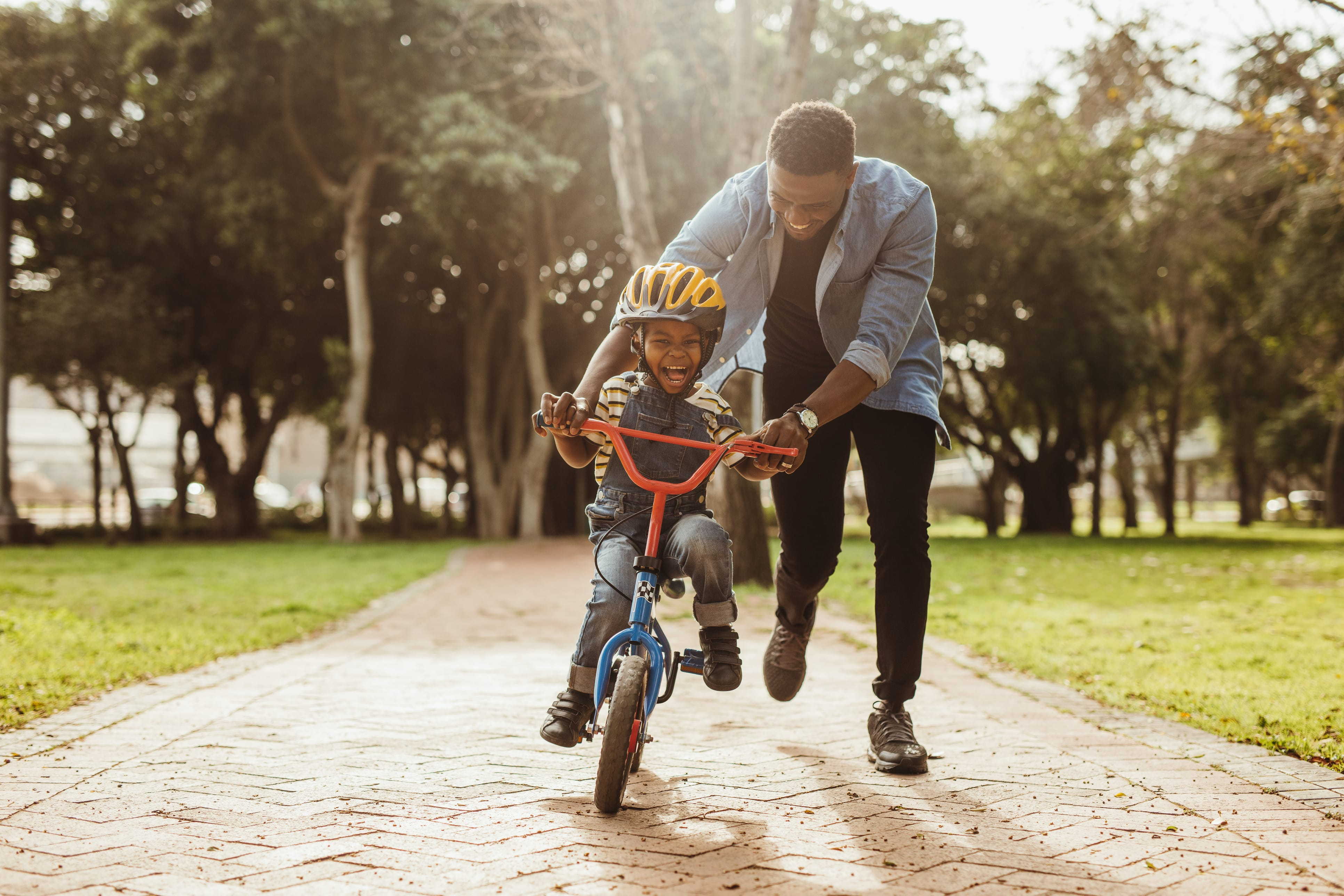 Man showing a young boy how to ride a bike