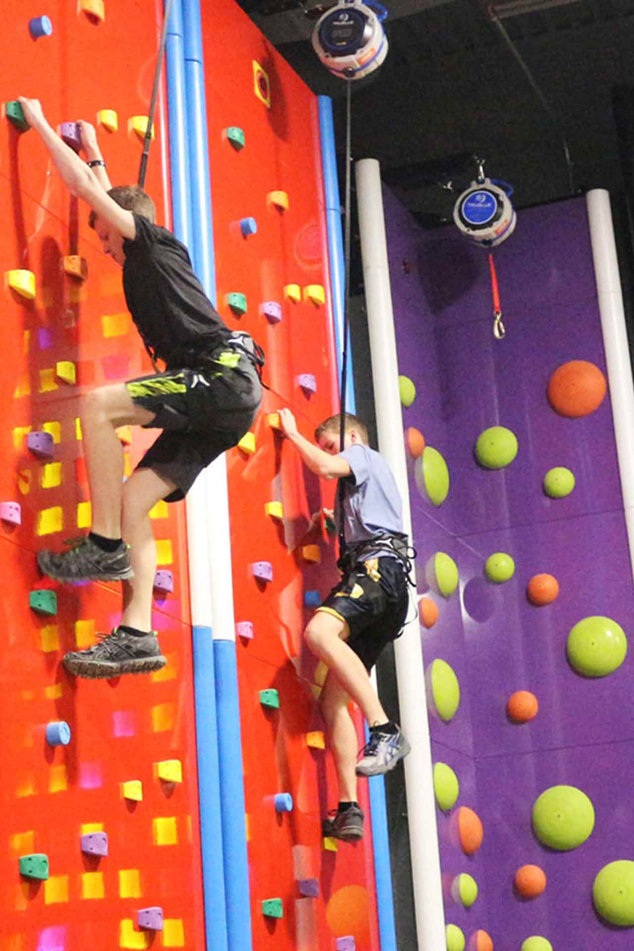 Two-kids-climbing-a-gym-wall