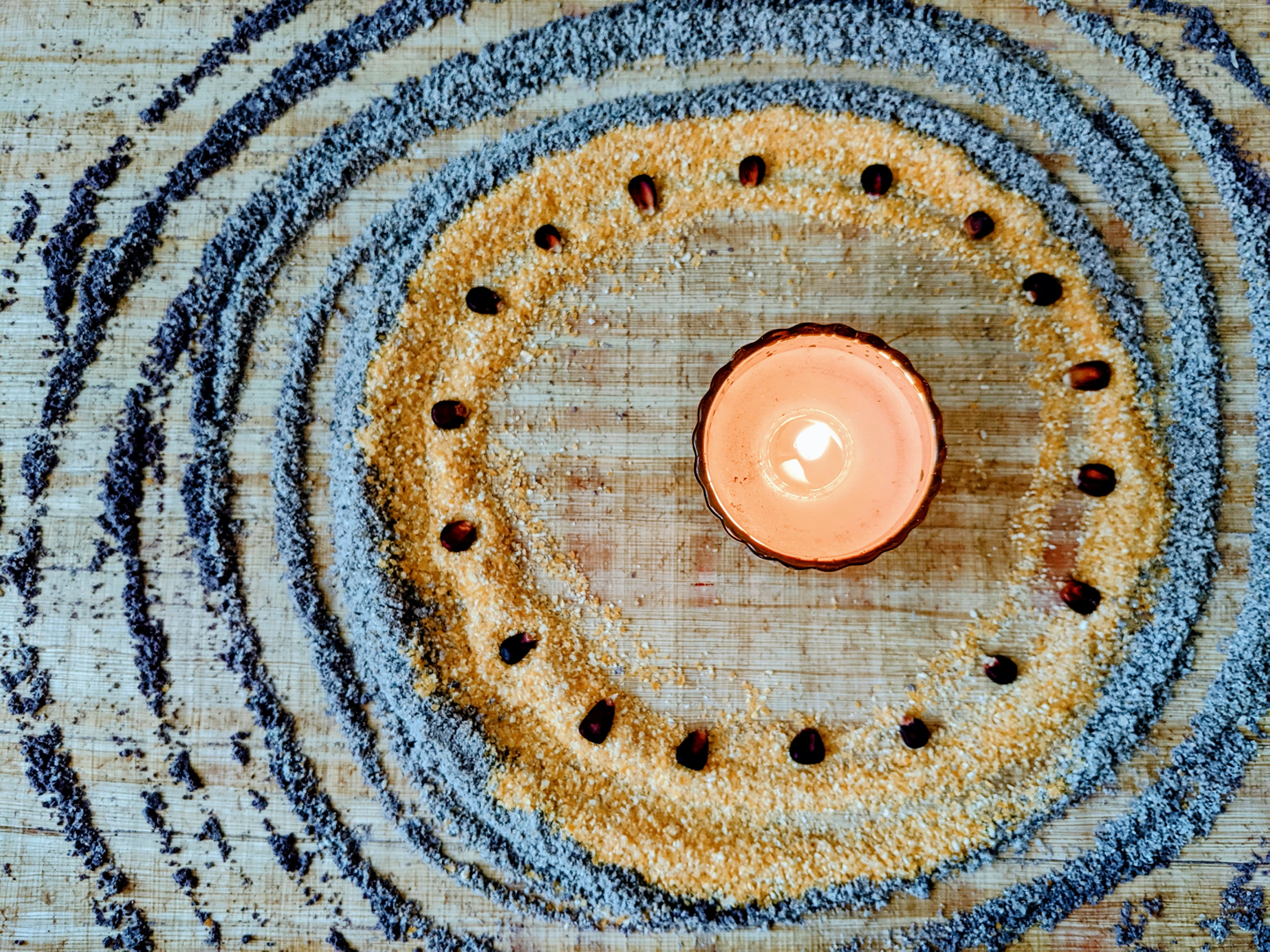 Photo of altar with a candle, blue cornmeal and red corn
