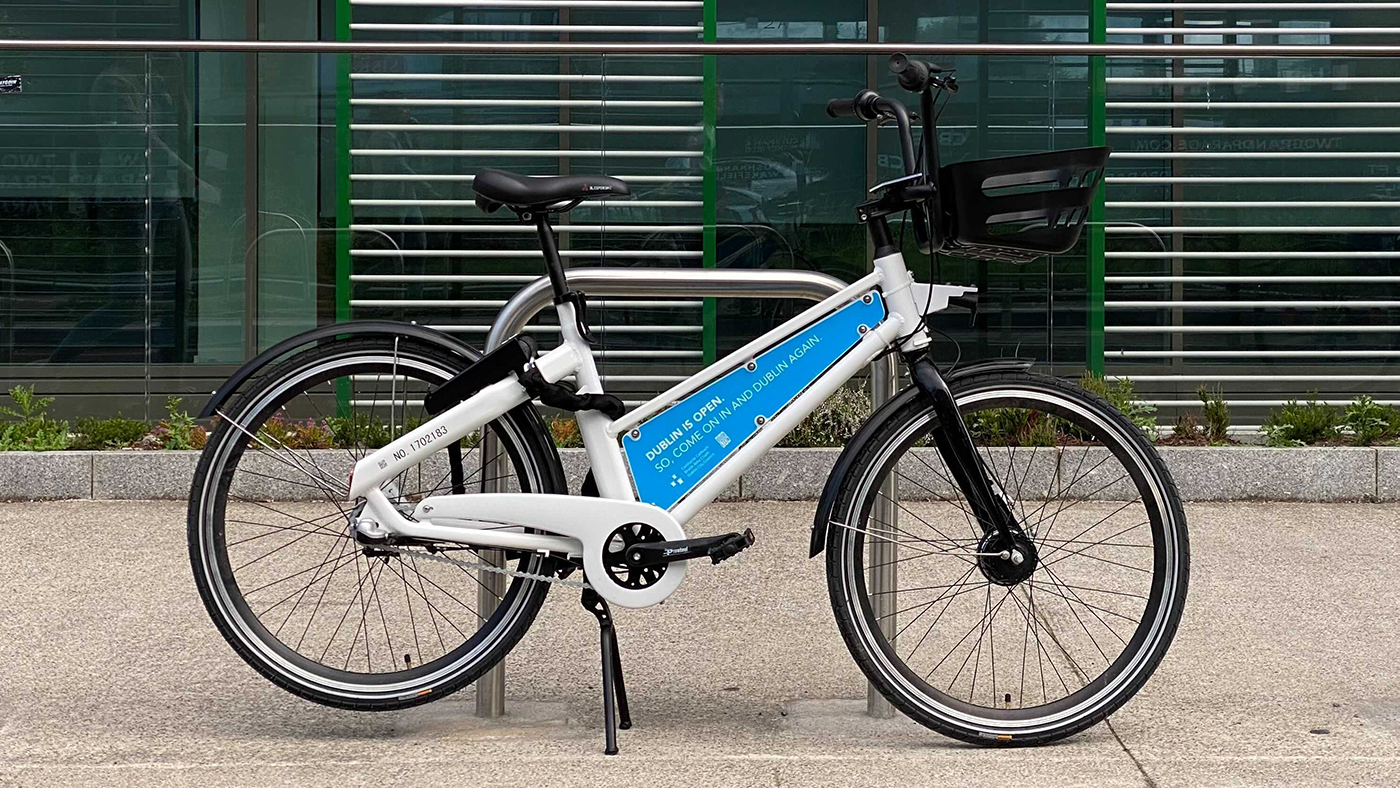 A Bleeper public rental bike featuring the new blue branding. The hire bike is parked next to a cycle parking stand.