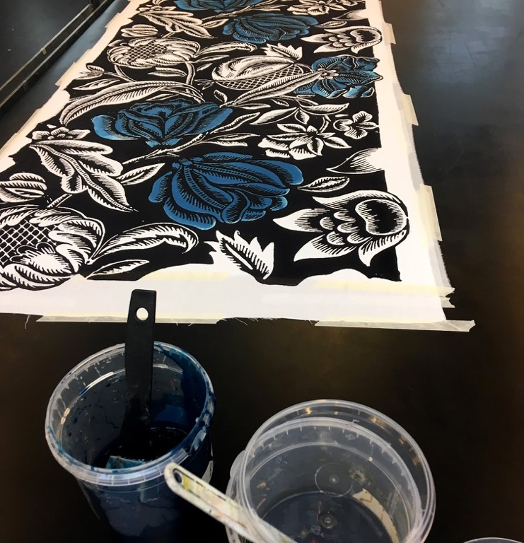A fabric with a traditional  flower pattern being painted blue