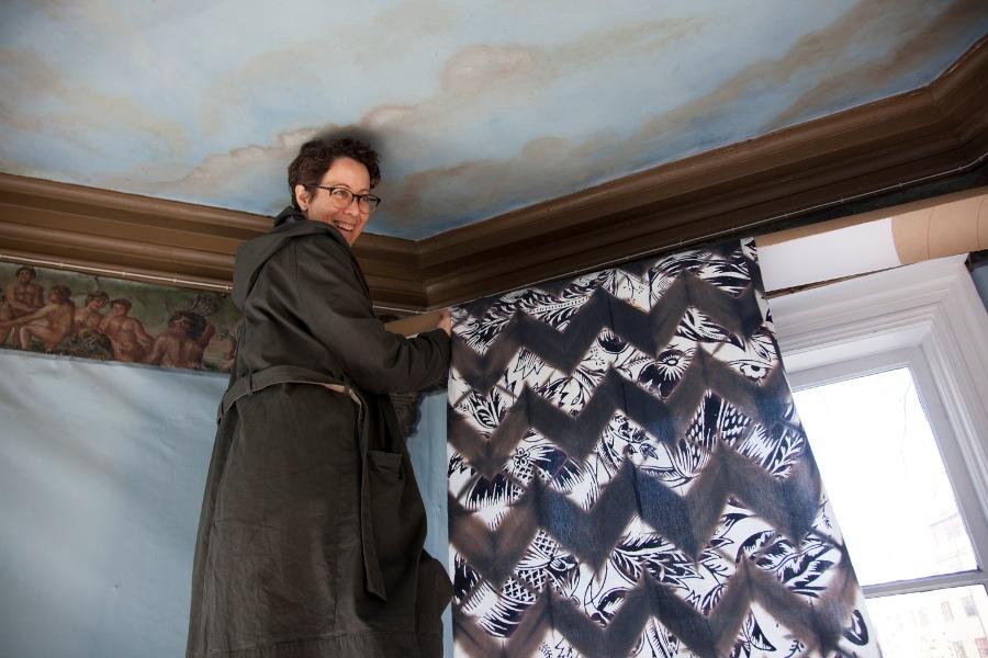 Textiel artist Elsa Chartin hanging one of her custom fabrics