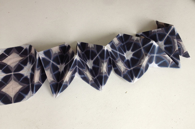 a blue and white shibori fabric folded like an origami