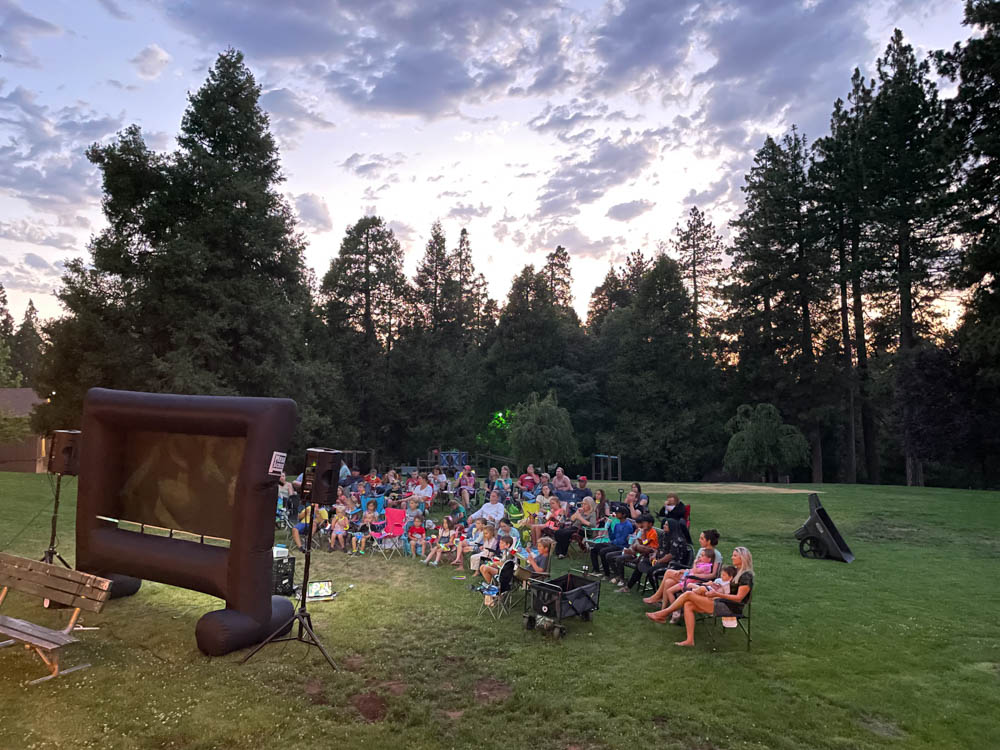 Scenic View of families sitting and enjoying a movie on a big grassy lawn.