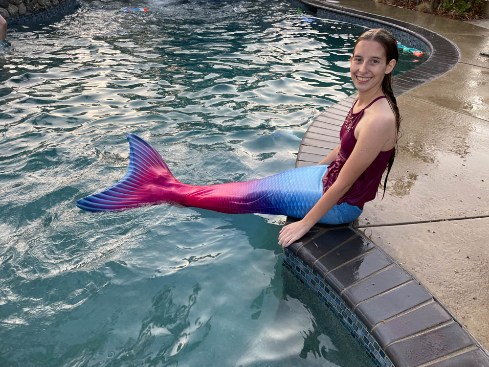 Girl wearing a mermaid tail by a pool