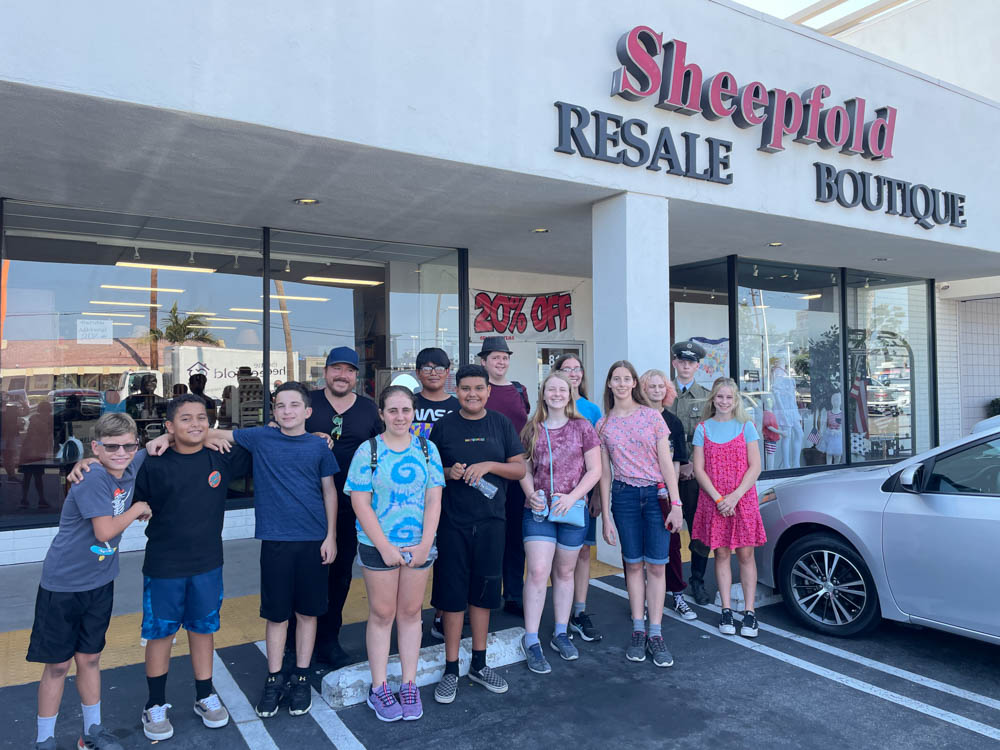 group of youth in front of a local ministry resale boutique