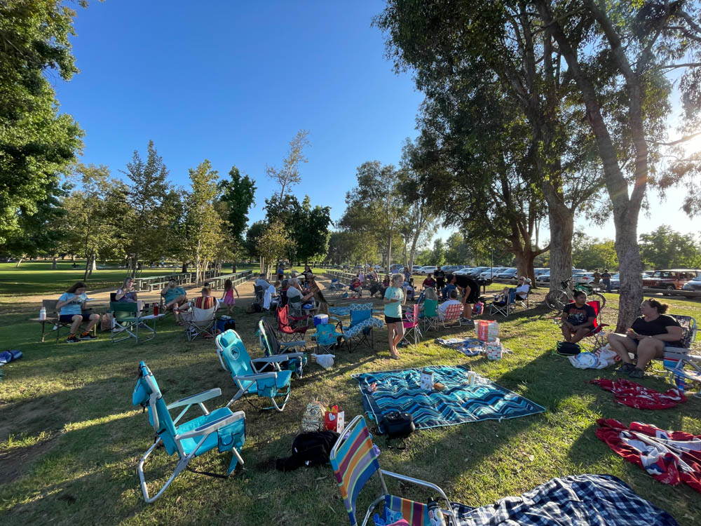 panoramic view of multiple families picnicking at the park